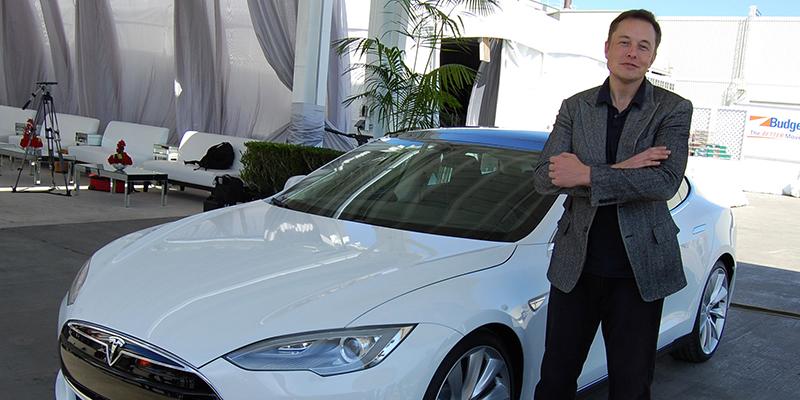 Elon Musk steht vor weißem Tesla