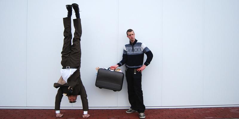 Mann macht Handstand und Mann mit Koffer