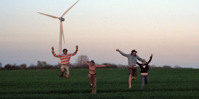 4 junge Erwachsene springen vor Windrad in die Luft