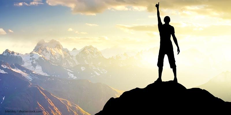 Mann steht triumfierend auf Berggipfel