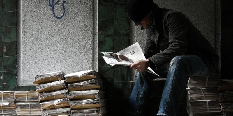 Mann sitzt auf Zeitungsstapeln und liest Zeitung