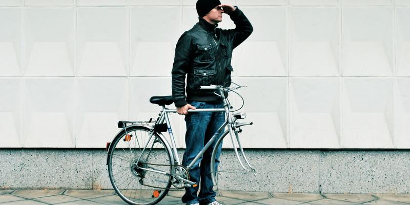 Mann mit Fahrrad ohne Vorderrad blickt in die Ferne