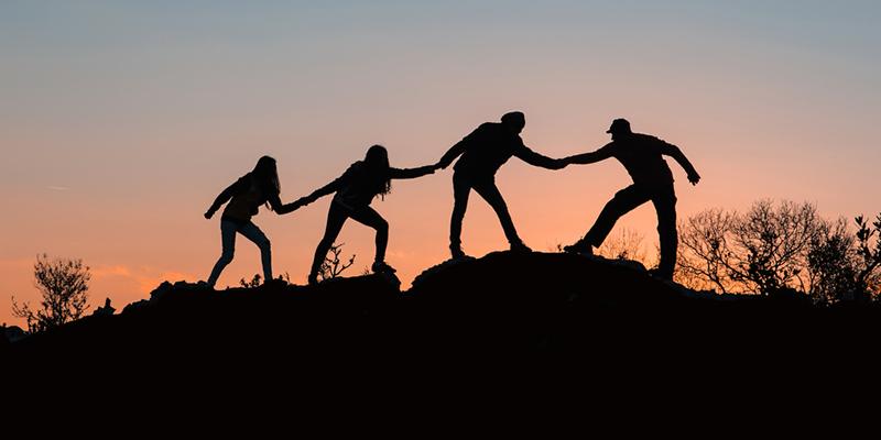 Vier Menschen halten sich an den Händen
