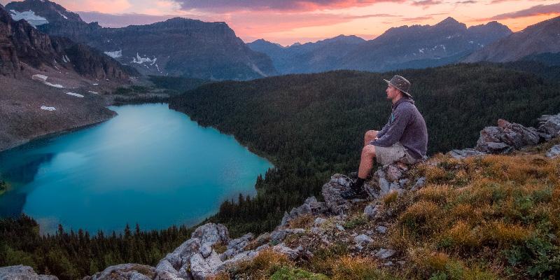 Mann sitzt auf einem Berg